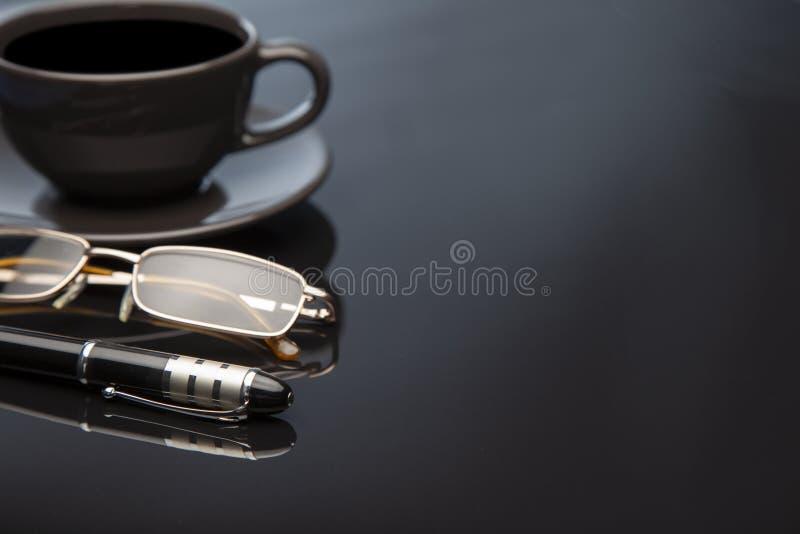 Tabela ou lugar do preto do ambiente de Workong com a pena dos vidros da xícara de café imagens de stock