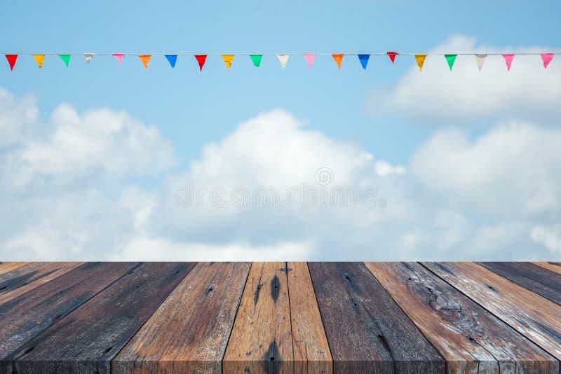 Tabela ou prancha de madeira vazia com c?u azul e nuvens e bandeira de papel colorida no fundo para a exposi??o do produto imagem de stock royalty free