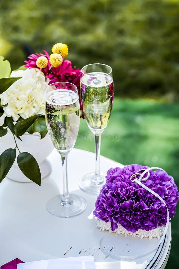 Tabela pequena com vidros com champanhe e alianças de casamento fotos de stock royalty free