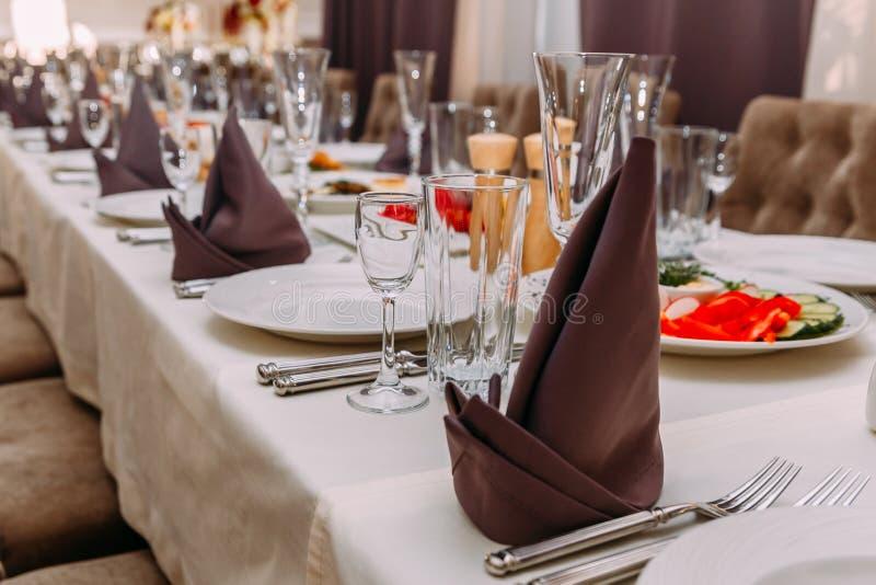 Tabela rica no restaurante, pratos brancos vazios, vidros de vidro, cutelaria fotografia de stock royalty free
