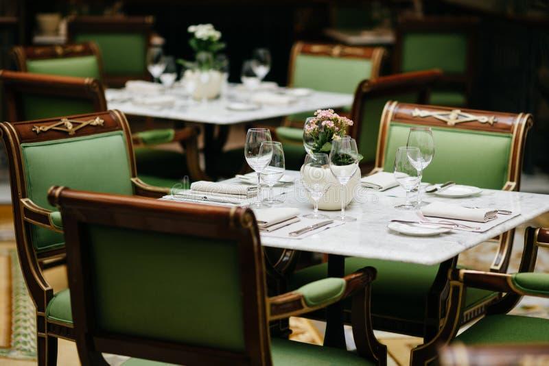 Tabela servida com vidros luxuosos, cutelaria, flores, cadeiras verdes ao redor no restaurante acolhedor Ninguém no tiro Tabela d imagens de stock royalty free