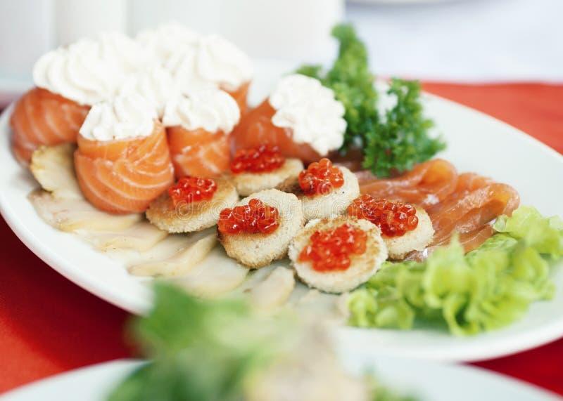 Tabela servida luxuosa com salmões e o caviar vermelho, salada na placa imagem de stock