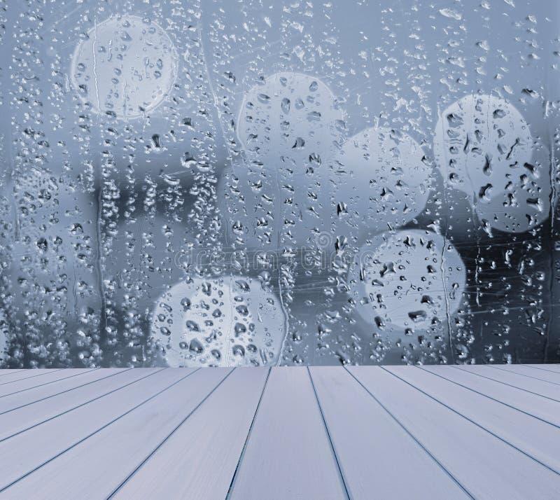 A tabela vazia com borrado, janela, chuva deixa cair o fundo, para o molde da exposição do produto fotografia de stock royalty free