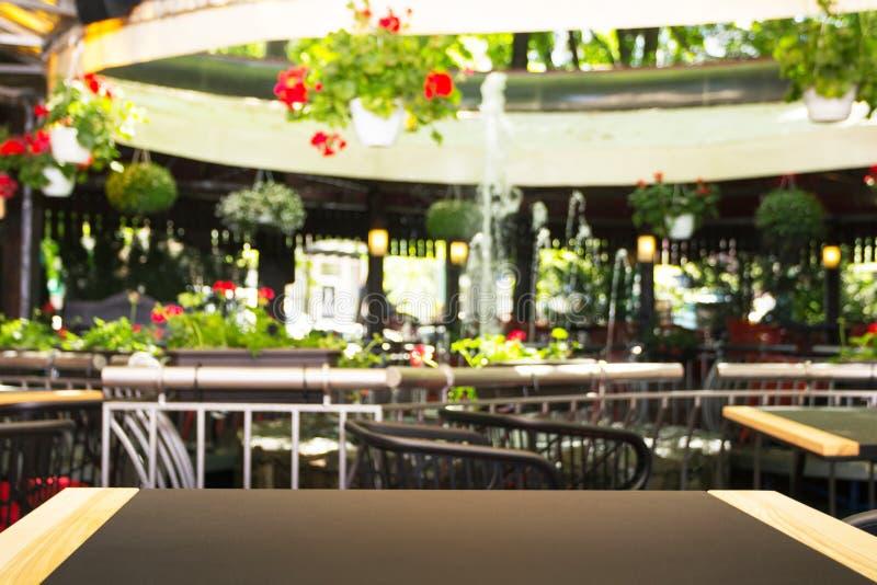 Tabela vazia na frente de um fundo borrado Um café claro da rua com flores, plantas e uma fonte - pode ser usado para indicar ou imagens de stock royalty free