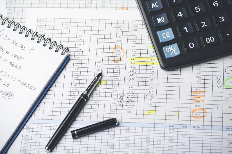 Tabelas com figuras de contabilidade, pena, caderno do papel e calculadora imagens de stock