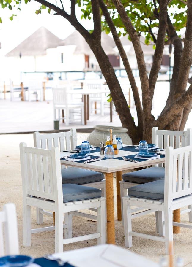 Tabelas de jantar ao ar livre na praia da areia fotografia de stock royalty free