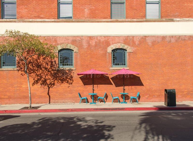Tabelas de turquesa e cadeiras, guarda-chuvas cor-de-rosa, janelas do segundo andar fotografia de stock royalty free