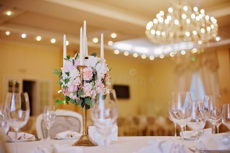 Tabelas do convidado com o castiçal na sala de banquete decorada rica do casamento foto de stock royalty free