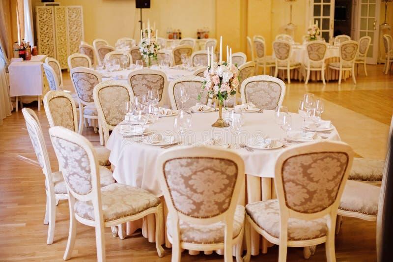 Tabelas do convidado com o castiçal na sala de banquete decorada rica do casamento imagem de stock royalty free
