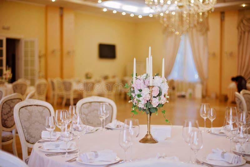 Tabelas do convidado com o castiçal na sala de banquete decorada rica do casamento fotos de stock royalty free