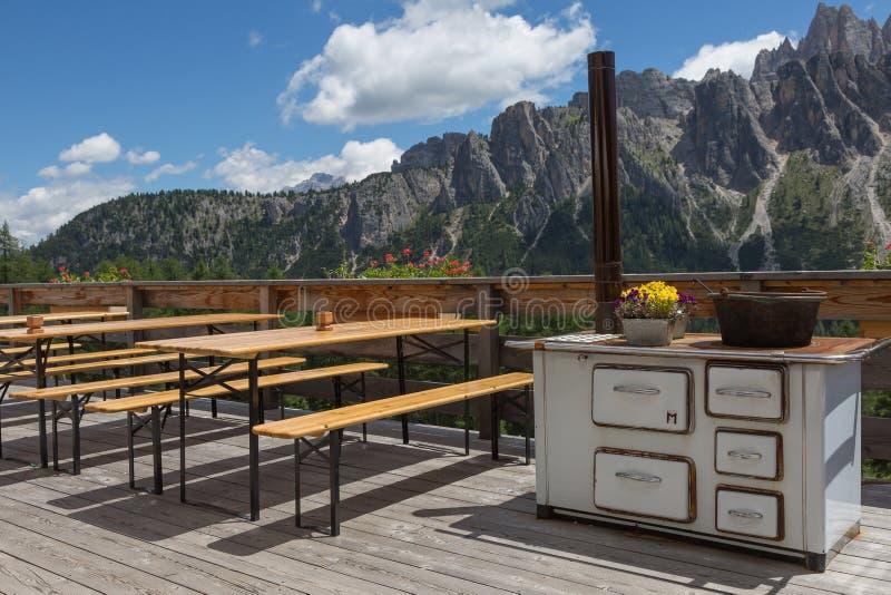 Tabelas e bancos de madeira fora no abrigo da montanha no cenário italiano dos cumes das dolomites imagens de stock royalty free