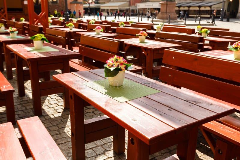 Tabelas e bancos de madeira grandes vazios em pedras de pavimentação em um café mim fotos de stock