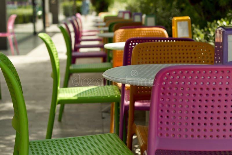 Tabelas e cadeiras coloridas plásticas no café imagens de stock royalty free