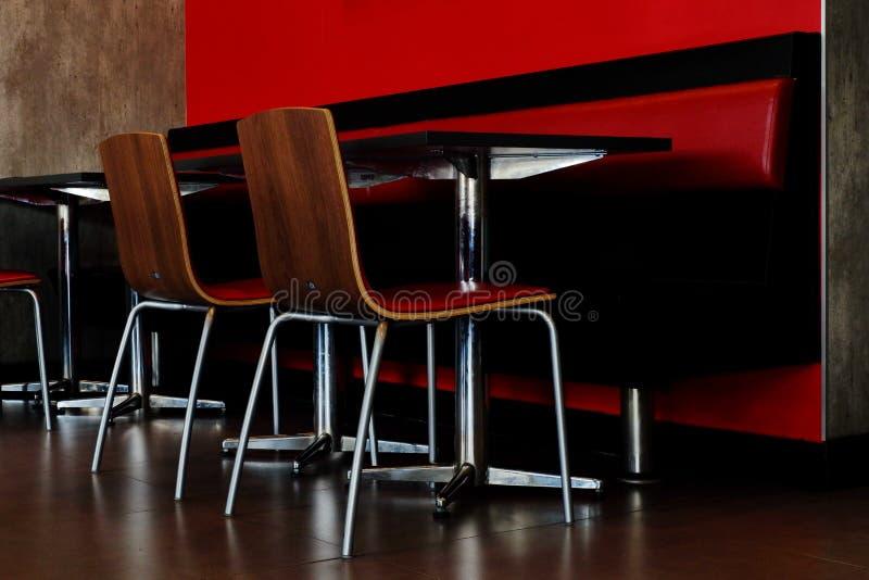 Tabelas e cadeiras na sala imagens de stock