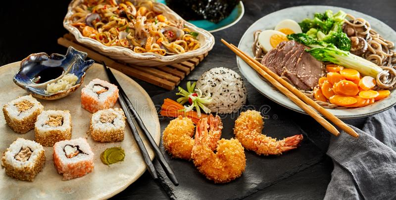 Tabelas espalhadas com culinária japonesa tradicional imagens de stock royalty free