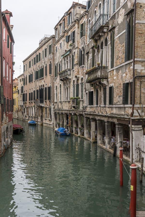 Tabelas na passarela coberta sob casas históricas no canal, Veneza, Itália imagem de stock