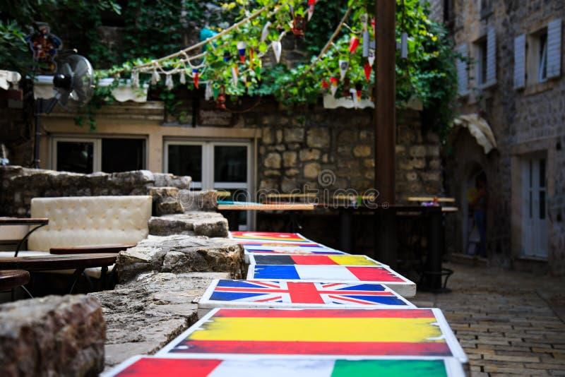 Tabelas no café da rua, pintado nas cores das bandeiras da Espanha diferente dos países, Reino Unido, França terrace imagens de stock