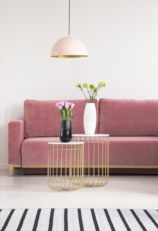 Tabelas pequenas douradas com flores, o sofá cor-de-rosa e o candelabro em um interior da sala de visitas Foto real fotografia de stock