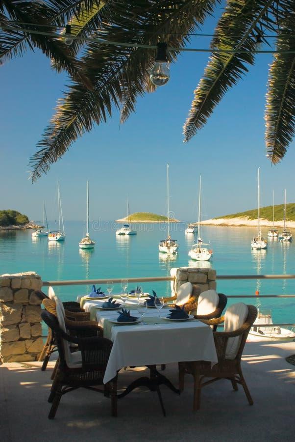 Tabelas seridas no restaurante da praia do clube yachting fotos de stock royalty free