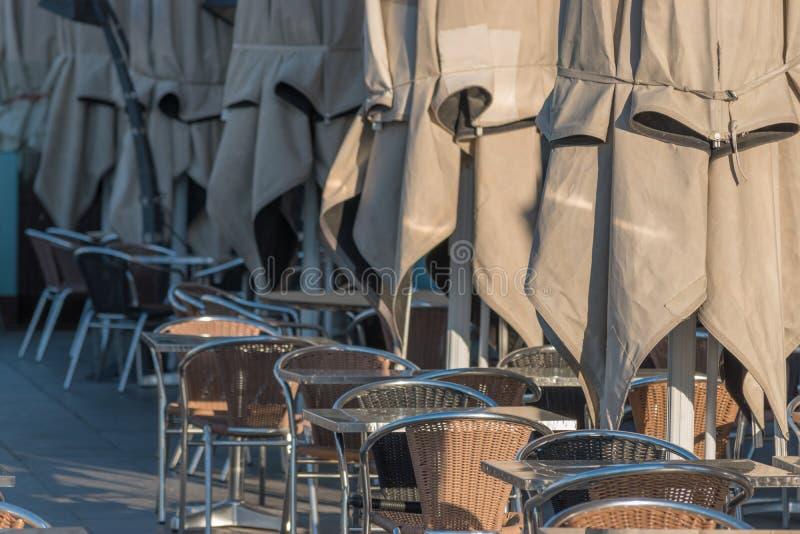 Tabelas vazias com os umbrelas no restaurante na rua durante o nascer do sol fotos de stock