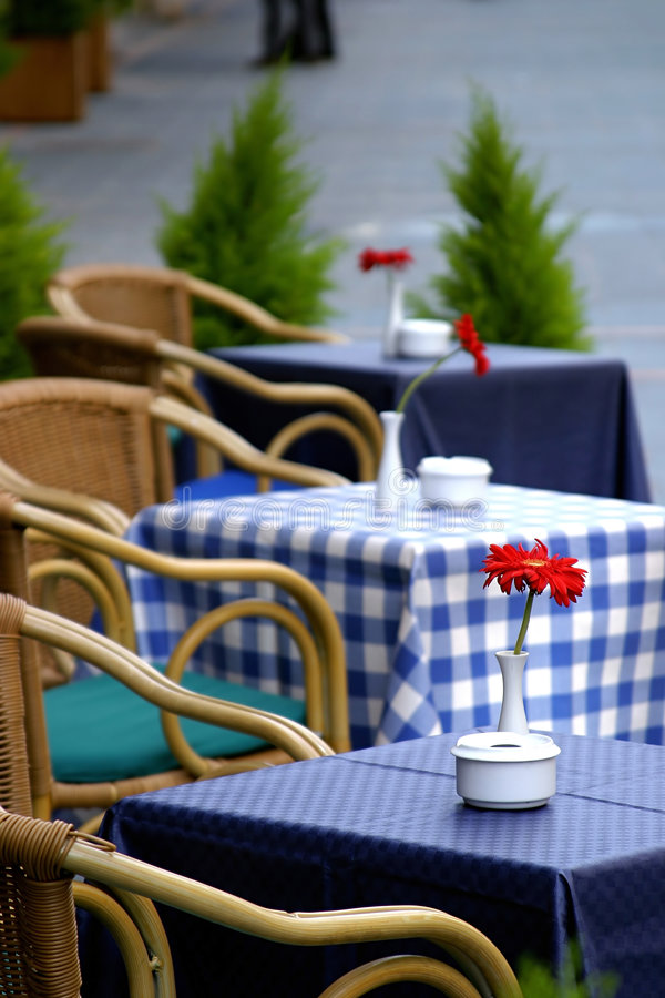 Tabelas vazias na rua com as rosas nelas fora de uma barra ou de um restaurante do café. fotografia de stock