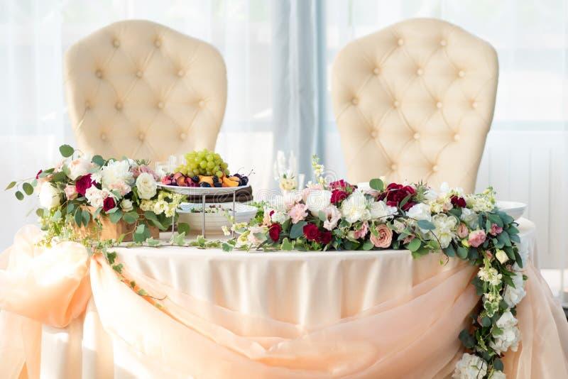 Tabell av bruden och brudgummen i restaurangen Bröllopdekor, blommor arkivfoton