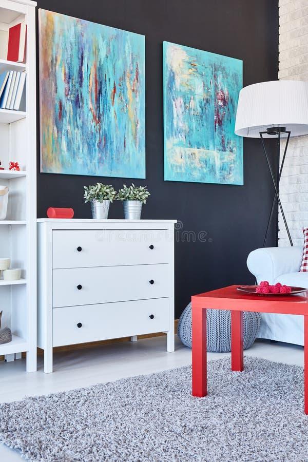 Tabell, byrå och målningar i ett rum royaltyfri foto