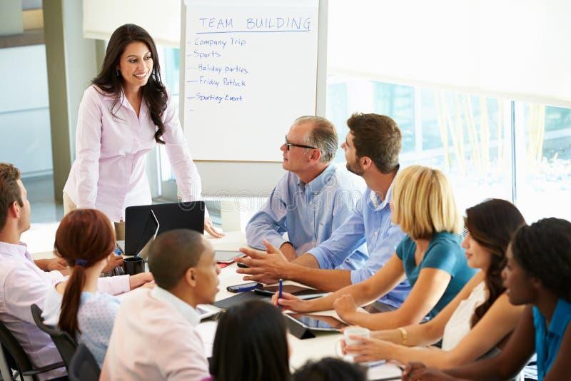 Tabell för affärskvinnaAddressing Meeting Around styrelse royaltyfria bilder