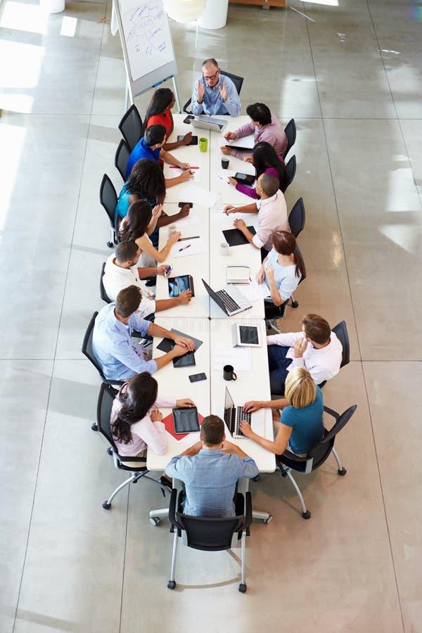 Tabell för affärsmanAddressing Meeting Around styrelse royaltyfri foto