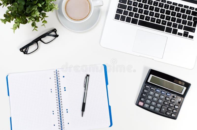 Tabell för kontorsskrivbord med bärbara datorn, kaffekoppen och bästa sikt för tillförsel royaltyfria foton