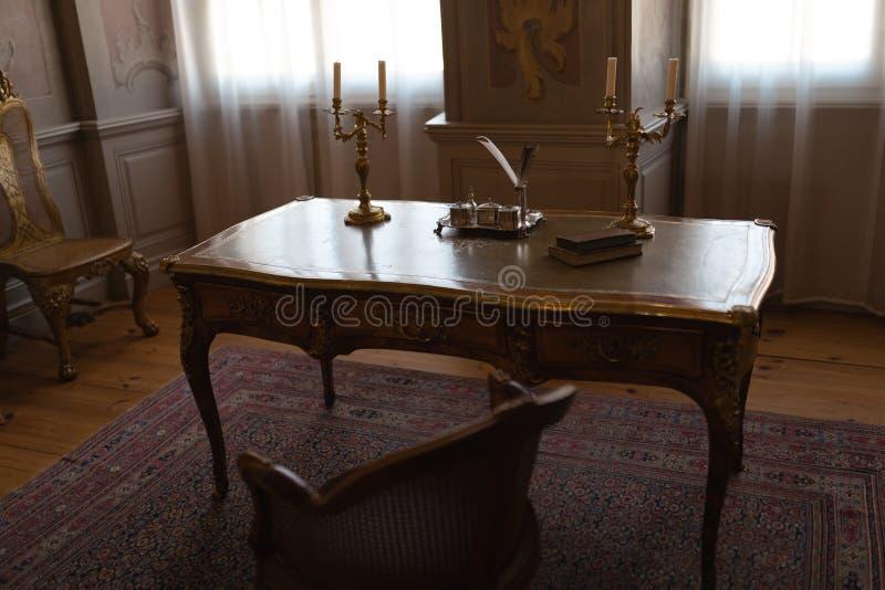Tabell för kunglig slott i ett kabinett rum med stolar och penna och färgpulver royaltyfri foto