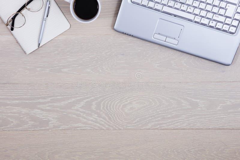 Tabell för träkontorsskrivbord med kaffe, bärbara datorn, pennblocket och exponeringsglas, tillförsel, bästa sikt med kopieringsu royaltyfri foto