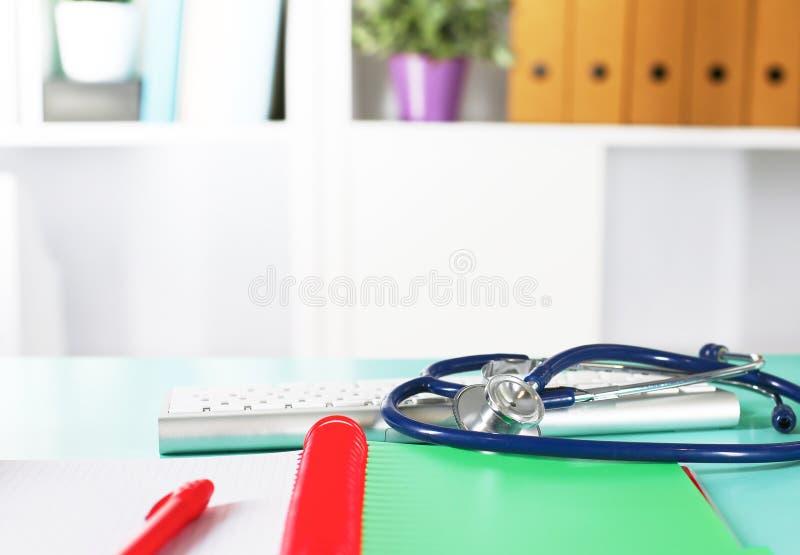 Tabell för workspace för doktors` s funktionsduglig med den tålmodiga formen för tomt papper för urladdning för ` s, medicinskt r royaltyfri fotografi