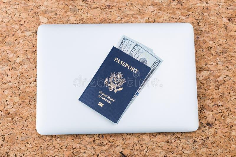 Tabell med bärbara datorn och passet royaltyfri foto