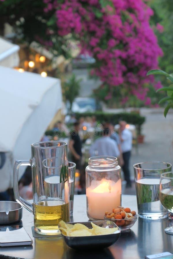 Tabell med drinkar och mellanmål och en stearinljus royaltyfria foton