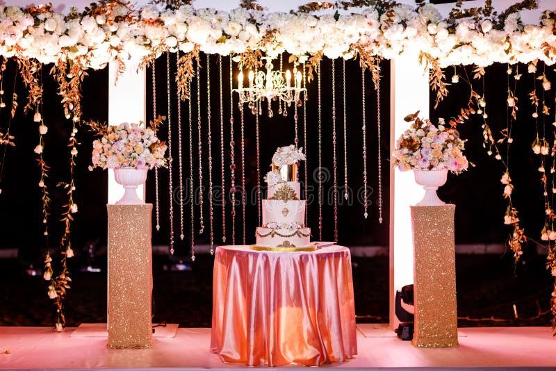 Tabell med en bröllopstårta, stearinljus, ljus och blommor bröllop för band för inbjudan för blomma för elegans för bakgrundsgarn royaltyfri foto