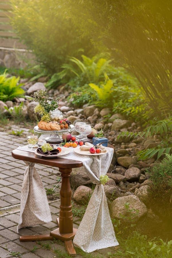 Tabell med festlig fest och bordduk i sommarträdgården arkivbild