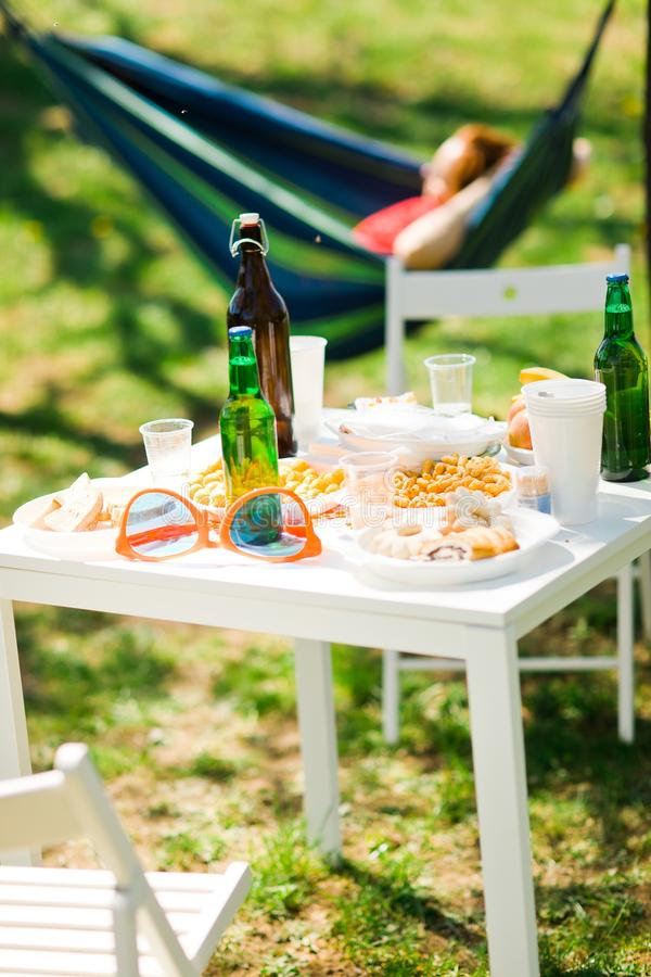 Tabell med flaskor av öl och mat på sommarträdgårdpartiet arkivbild
