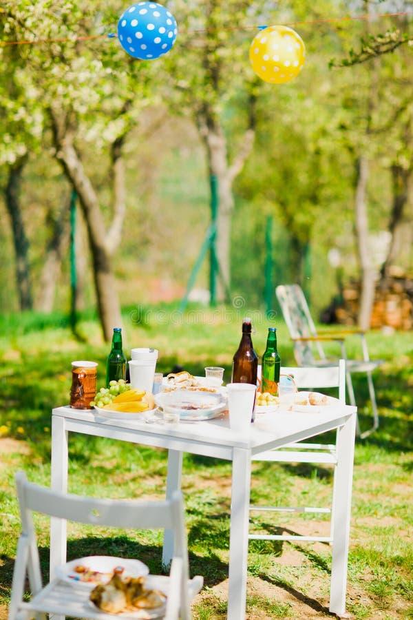 Tabell med flaskor av ?l och mat p? sommartr?dg?rdpartiet arkivbilder