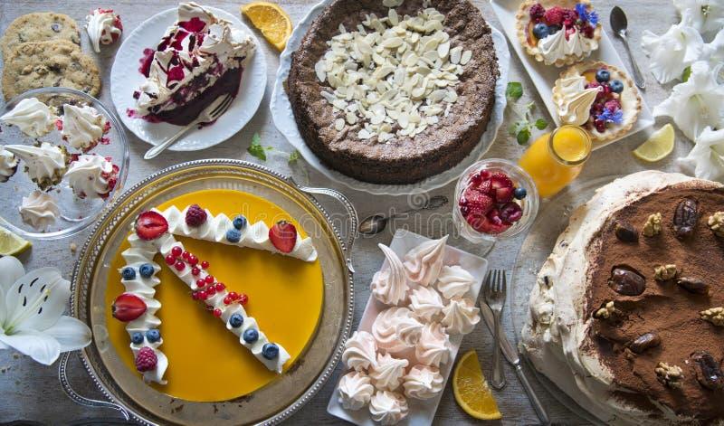 Tabell med påfyllningar av kakor, muffin, kakor, cakepops, efterrätter, frukter, blommor och orange fruktsaft royaltyfri foto