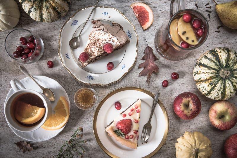 Tabell med påfyllningar av te, kakor, muffin, efterrätter, frukter, blommor och forntida skedar och ett päron, äpplen och pumpor fotografering för bildbyråer