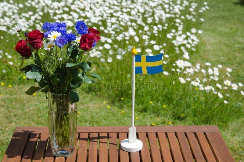 Tabell med sommarblommor och en svensk flagga royaltyfria bilder