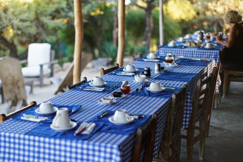 Tabell med tomma plattor och kaffekoppar, blå rutig bordduk, suddig person i bakgrund som har morgon royaltyfri bild