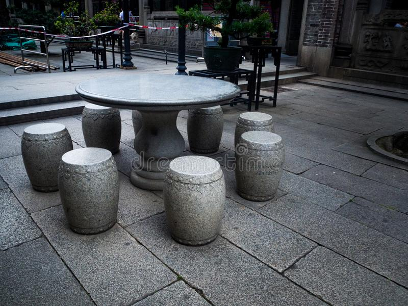 Tabell och bänkar som göras av stenen i trädgården kinesisk stil royaltyfri fotografi