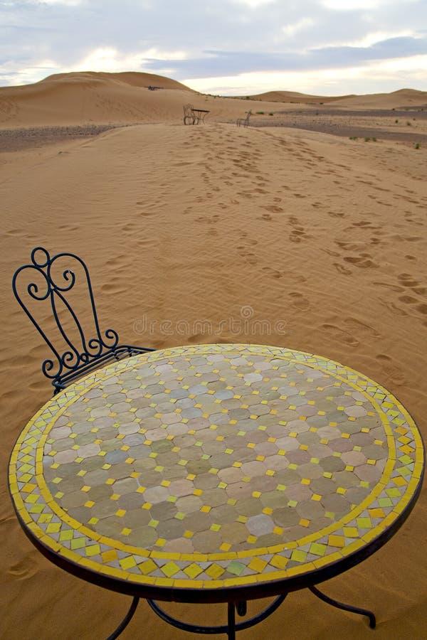 Tabell och plats i sand arkivfoto