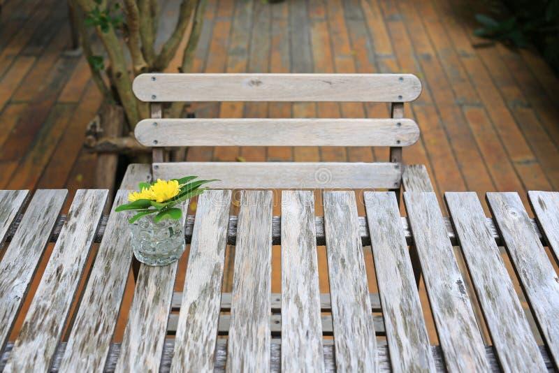 Tabell och stol för gammal stil träi trädgården med exponeringsglas av blommagarnering arkivbilder