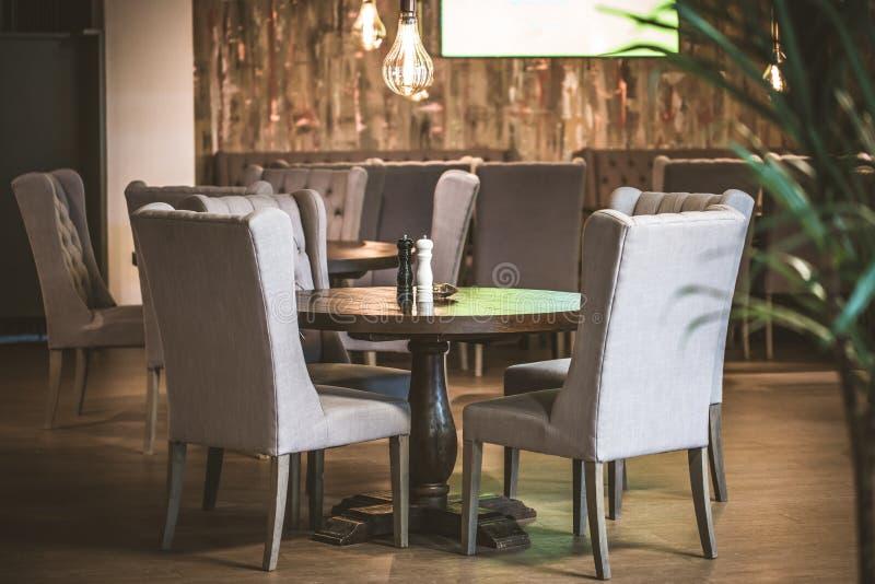Tabell och stolar för modernt kafé inre med ljusa kulöra väggar royaltyfria foton