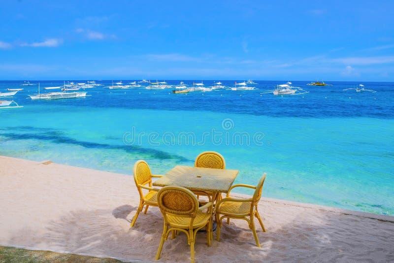 Tabell och stolar på den tropiska stranden royaltyfri bild