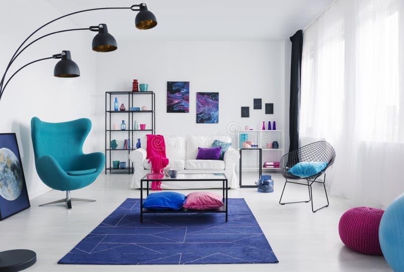 Tabell på blå matta bredvid fåtöljen i modern vardagsrum som är inre med affischer och lampan Verkligt foto arkivbild