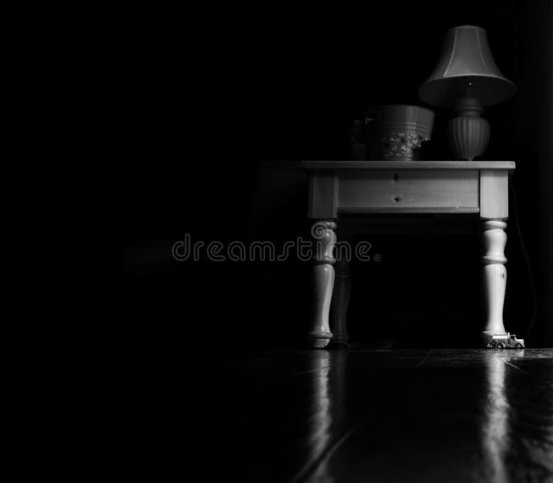 Tabell på natten med kökljus som skiner på det royaltyfria foton